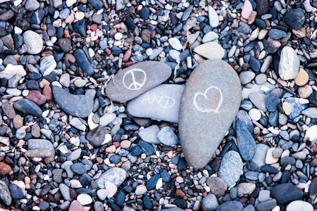 humanitarian: Peace and Love symbols on rocks in nature Stock Photo