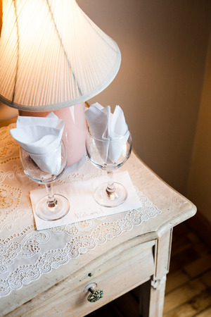 bedside: Welcome Card on a Bedside Table with two Empty Wine Glasses Stock Photo