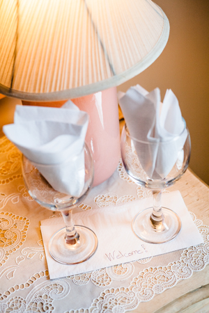 bedside table: Welcome Card on a Bedside Table with two Empty Wine Glasses Stock Photo