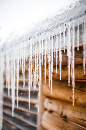 heat loss: Long Icicles Melting of a Log Wood Chalet roof top Stock Photo
