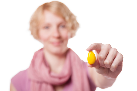 Young Woman Holding a Yellow Easter Egg in front of the Cameras - Isolated on White Background photo
