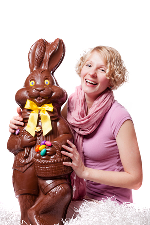 Girl Laughing and Holding a HUGE Chocolate Easter Bunny Isolated On White Background photo