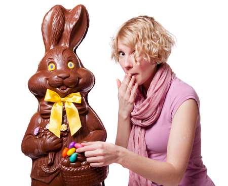 chocolate eggs: Blond Girl stealing Easter Eggs of a Chocolate Bunny Isolated on White Background Stock Photo