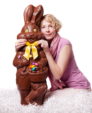 Blond Girl Adjusting Bowtie of a Chocolate Easter Bunny Isolated on White Background Banque d'images