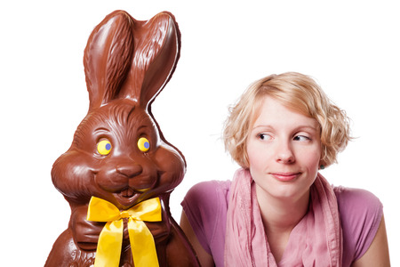 Chocolate Easter Bunny and a Blond Girl Looking at each other. Isolated Over White photo