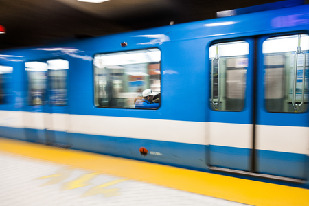 Editorial - Montreal, Canada. Fast Matro Train with Motion Blur Passing at the Station During a winter day.