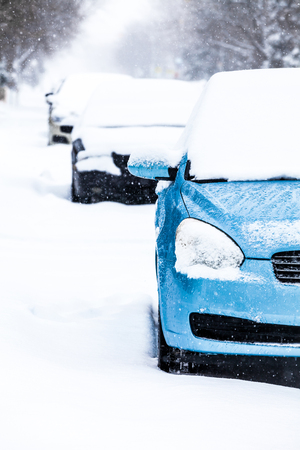 Parked Cars in the Street on a Snowstorm Winter Day photo