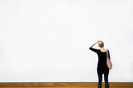 Caucasian Young Blond Woman Questioning in front of a Blank Wall in a Museum 스톡 콘텐츠
