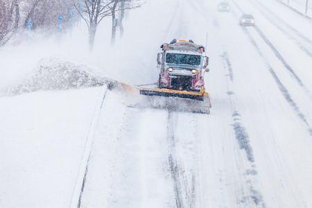 Snowplow Truck Removing the Snow from the Highway during a Cold Snowstorm Winter Day photo