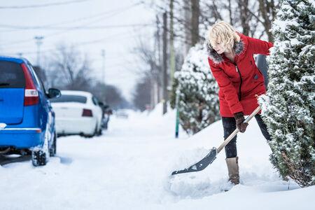 neige qui tombe: Femme Pelleter son stationnement apr�s une temp�te de neige