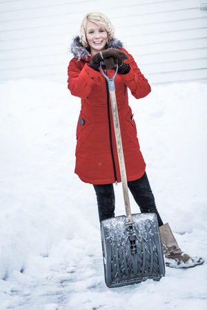 Happy Woman with a Shovel in a Parking lot. Shes done with shoveling for today ! photo