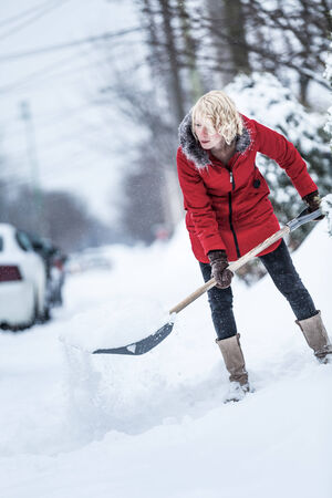 Woman Shoveling her Parking Lot after a Snowstorm photo