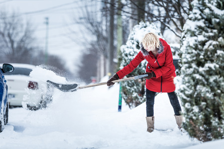 neige qui tombe: Femme Pelleter son stationnement après une tempête de neige