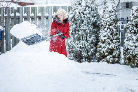 Woman Shoveling her Parking Lot after a Snowstorm Reklamní fotografie