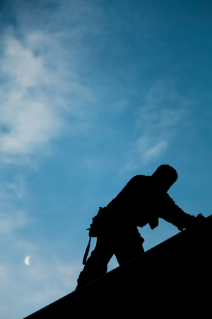 roofer: Contractor in Silhouette working on a Roof Top with blue Sky in Background
