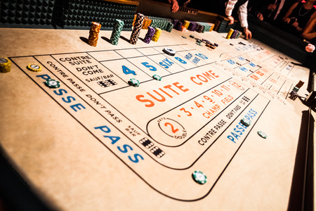 Craps Table, Chips Piles and People Gambling all Around Stock Photo