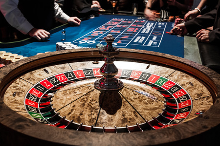roulette wheels: Wooden Shiny Roulette Details in a Casino with Blurry People and Croupier in Background Stock Photo