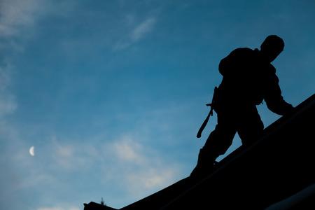 Aannemer in Silhouet werken op een dak met blauwe hemel op achtergrond