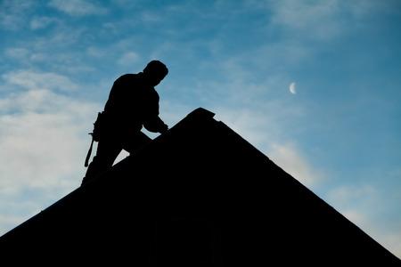 alba�il: Contratista en la silueta trabajando en un techo con cielo azul de fondo Foto de archivo