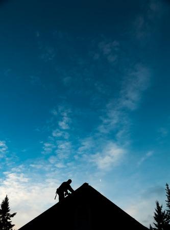 Aannemer in Silhouet het werken op een dak met blauwe hemel op achtergrond Stockfoto