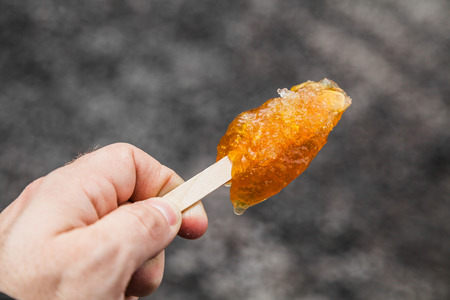 Hand Holding Maple Taffy on a wood stick photo