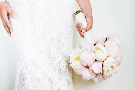 bridal bouquet: Woman Holding a nice Wedding Bouquet in front of a white Wall Stock Photo