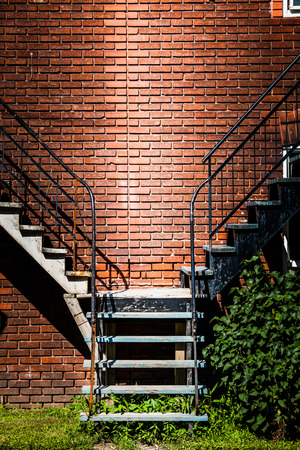 Symmetrical Staircases merging together and brick wall Stock Photo