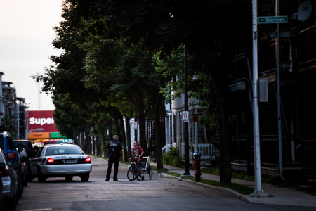 destitution: Editorial - July 24, 2014. Trois-Riviere, Quebec, Canada. Cop talking to a man in the street in the Poor Old Trois-Riviere Area where the poverty is always present, but where the houses are hystorical.