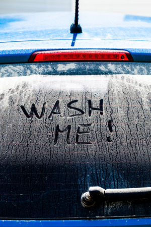 Wash Me Words on a Dirty Rear Car Window photo