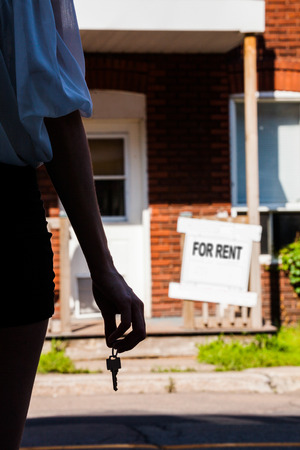 Young Woman standing with keys in front of her new apartment photo