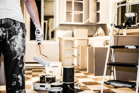 Lío de todo tipo de equipo de pintura en la cocina y el hombre desalentado Foto de archivo - 33516659