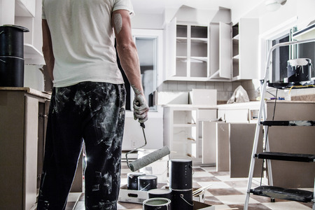 habitacion desordenada: Lío de todo tipo de equipo de pintura en la cocina y el hombre desalentado Foto de archivo