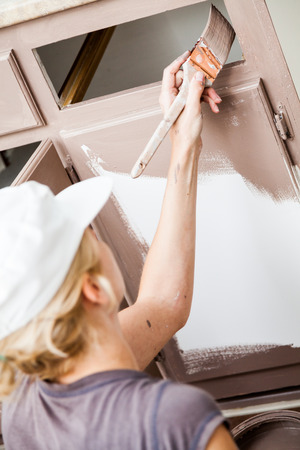 Closeup of Woman Holding Paint Brush and Painting Kitchen Cabinets Stock Photo
