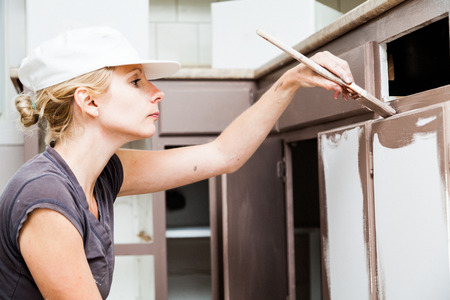 Closeup of Woman Holding Paint Brush and Painting Kitchen Cabinets 스톡 콘텐츠