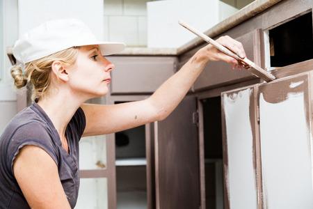 peintre en b�timent: Gros plan d'une femme tenant un pinceau et peinture Armoires de cuisine