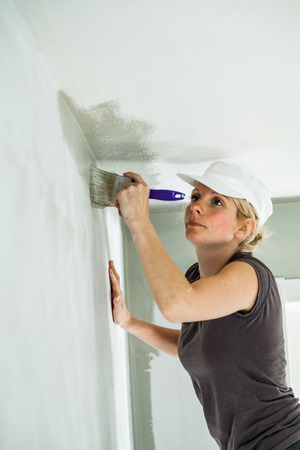 decorator: Woman Painting the Edges of the Ceiling with Paintbrush