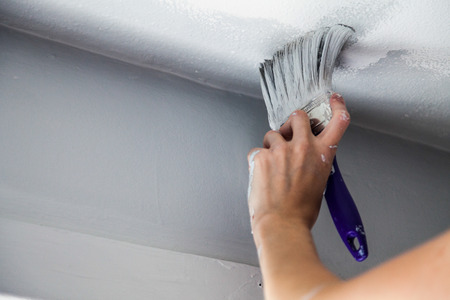 Painting the Edges of the Ceiling with Paintbrush Stock Photo