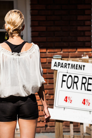 for rent sign: Young Woman standing with keys in front of her new apartment Stock Photo