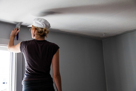 ceiling construction: Woman Painting the Edges of the Ceiling with Paintbrush