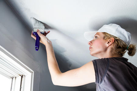 ceiling design: Woman Painting the Edges of the Ceiling with Paintbrush