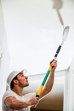 painter and decorator: Closeup of Man Holding Roller Pin and Painting the Ceiling