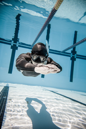freediver: Freediver Holding his breath and Performing during a AIDA DYN Freediving Competition