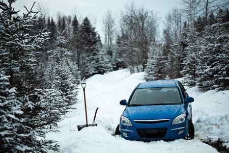 どこの途中で林道に雪の中で立ち往生している車。 写真素材