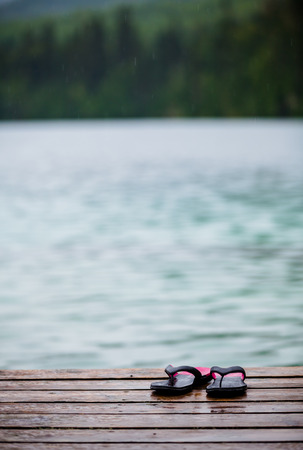 turquoise water: Flip flops on a Dock in front of a Turquoise Water Lake in the Wild Nature Stock Photo