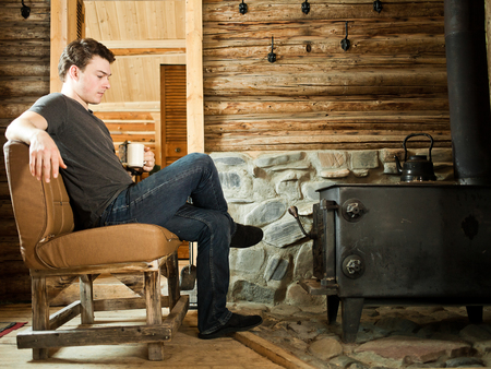 Lonely Man sitting in front of a Slow Combustion Stove and Relaxing with Slippers and Cup of Coffee.