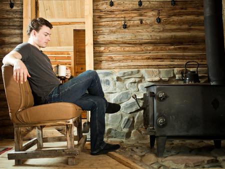 Hombre solo que se sienta delante de una estufa de combustión lenta y relajante, con zapatillas y una taza de café. Foto de archivo - 37165493