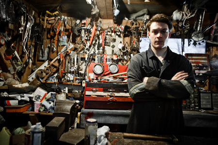 dirty old man: Arm Crossed Worker in a Shed and Lots of Tools Hanging on the Wall