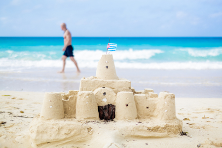 sandcastle: Cuban Sandcastle with the country Flag on one of the most Beautiful Beach of Cuba with a tourist in background Stock Photo