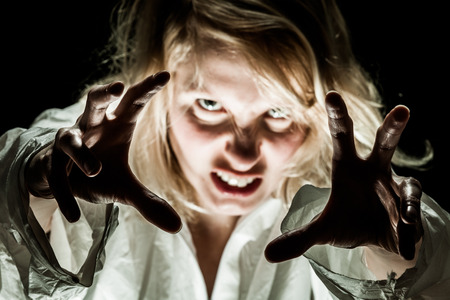 schizophrenia: Crazy Woman acting like a Zombie - focus on hands Stock Photo