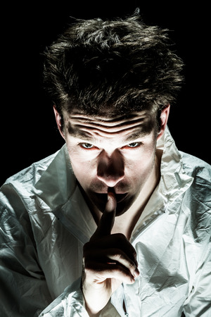 psychopath: Psycho Man Asking for Silence with Finger on Lips